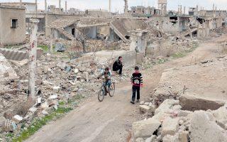 Παιδιά παίζουν στους δρόμους της κατεχόμενης από τους αντάρτες ερειπωμένης ιστορικής πόλης Μπόσρα αλ Σαμ, στην επαρχία της Ντερά στη νότια Συρία.