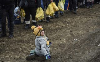 A child cries as she waits with other migrants and refugees for security check after they crossed the Macedonian border into Serbia, near the village of Miratovac, on January 26, 2016.