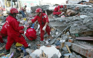 Taiwanese rescuers clear rubble from a collapsed building after a 6.7 magnitude earthquake struck, Wednesday, Dec. 27, 2006, in Pingtung County, 350 kilometers (217 miles) south west of Taipei, Taiwan. Taiwan's telephone communications with neighboring Asian countries were cut off Wednesday, hours after a powerful earthquake struck the southern part of the island, killing two and triggering a regional tsunami alert. The quake, which hit late Tuesday, came on the second anniversary of the devastating tsunami that took more than 200,000 lives in southern Asia. (AP Photo/David Lee) **Taiwan Out**