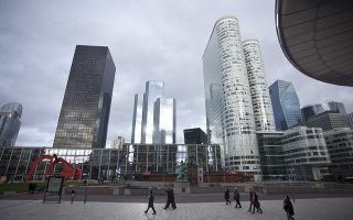 Pedestrians walk in a plaza as skyscrapers stand beyond in the La Defense business district in Paris, France, on Wednesday, Jan. 8, 2014. France's trade deficit continues to widen, as high payroll taxes and inflexible labor rules price French-made goods out of the market. Photographer: Balint Porneczi/Bloomberg