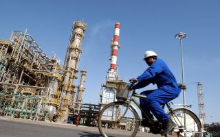 Passing the furnace stack, Savio Menezes, a refinery operator rides a bicycle at an oil processing plant in Jebel Ali Free Zone  in Dubai, United Arab Emirates, Thursday June 3, 2004. (AP Photo/Kamran Jebreili)