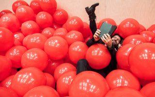 Χίλιες κόκκινες πλαστικές μπάλες γεμίζουν τον χώρο στη Στέγη, θυμίζοντας σχολική αίθουσα και φέρνοντας στον νου παιδικά παιχνίδια.
