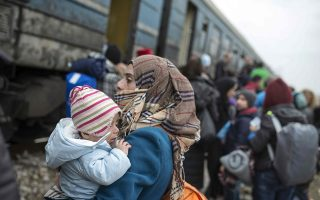 A woman holds a child as migrants and refugees board a train heading to Serbia from the Macedonian-Greek border near Gevgelija on February 18, 2016.  The police chiefs of five countries on the migrant route through southeast Europe announced a new agreement on February 18 for a coordinated registration point for refugees at the Greek-Macedonian border. / AFP / Robert ATANASOVSKI