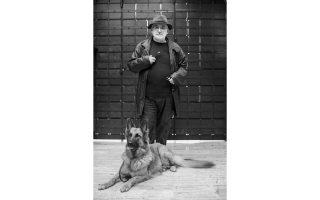 Ο Θάνος Μικρούτσικος μαζί με τη Σίλα, η οποία συμβιώνει αρμονικά με τους δύο του γάτους, στο προαύλιο του σπιτιού του στο Μετς.