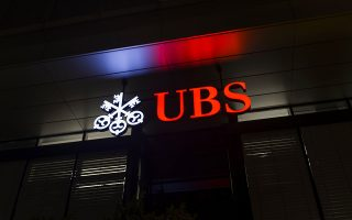 A picture taken on February 25, 2016 shows the logo of the Swiss global financial services company UBS at the entrance of a branch's building in Zurich. / AFP / FABRICE COFFRINI