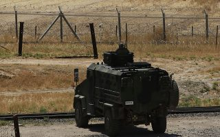 In this photo taken from the Turkish side of the border between Turkey and Syria, in Akcakale, southeastern Turkey, a Turkish soldier on an armoured personnel carrier secures the border as in the background, top right, a flag of the Kurdish People's Protection Units, or YPG, files over the town of Tal Abyad, Syria, Tuesday, June 16, 2015.  Kurdish fighters with the YPG along with their allies Free Syrian Army, took full control of Tal Abyad, on Tuesday, dealing a major blow to the Islamic State group's ability to wage war in Syria.  Mopping up operations have started to make the town safe for the return of residents, after more than a year of State group militants holding control of the town.  (AP Photo/Lefteris Pitarakis)