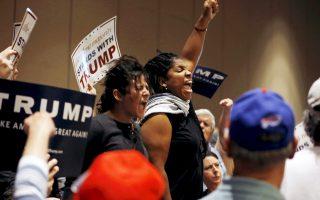 Διαδηλωτές κατά της υποψηφιότητας του Ντόναλντ Τραμπ «συνοδεύονται» εκτός αιθούσης σε προεκλογική συγκέντρωσή του στην Τάμπα της Φλόριντα, τη Δευτέρα.