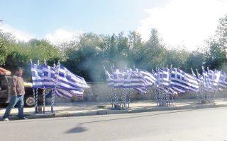 Γαλανόλευκες σημαίες με τον Σταυρό, ανεμίζουν στο αεράκι στη Xαριλάου Tρικούπη, τιμώντας τ' όνομα (και το «δυστυχώς, επτωχεύσαμεν»).