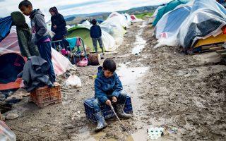 Ενα παιδί παίζει με τα λασπόνερα, στον καταυλισμό της Ειδομένης.