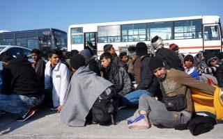 Πρόσφυγες και μετανάστες στο λιμάνι της Μυτιλήνης περιμένουν να επιβιβαστούν σε λεωφορεία με προορισμό το hotspot της Μόριας.