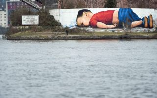 epa05206150 The photo of the dead Syrian boy Aylan Kurdi served as a template for a graffiti that artists Justus Becker and Oguz Sen sprayed at the harbour in Frankfurt (Main), Germany, 11 March 2016. Artists Justus Becker and Oguz Sen needed about 40 hours to finish the 120 square meters sized artwork.  EPA/ARNE DEDERT