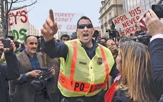 Αστυνομικός προσπαθεί να χωρίσει τα αντίπαλα «στρατόπεδα» οπαδών και αντιπάλων του Ερντογάν έξω από το Ινστιτούτο Brookings της Ουάσιγκτον.