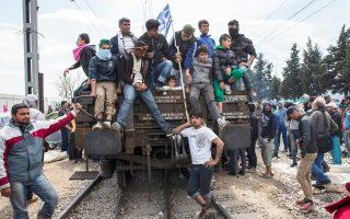 Πρόσφυγες και μετανάστες με την ελληνική σημαία πάνω σε βαγόνι του ΟΣΕ, στην Ειδομένη.