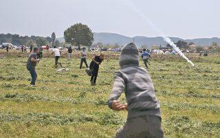 Μετανάστες και ακτιβιστές τρέχουν μακριά από τα δακρυγόνα που ρίχνουν αστυνομικοί της ΠΓΔΜ προκειμένου να σταματήσουν τον πετροπόλεμο και να απομακρύνουν τους πρόσφυγες από τον φράχτη.
