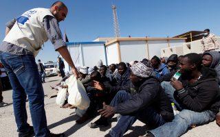 Λίβυος λιμενικός προσφέρει τρόφιμα σε πρόσφυγες, λίγο μετά τη διάσωσή τους ανοικτά της Τρίπολης.