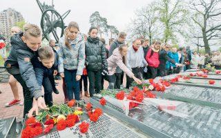 Παιδιά από την Ουκρανία καταθέτουν λουλούδια στο μνημείο για τους ανθρώπους που σκοτώθηκαν, στο κέντρο του Κιέβου. Ακόμα και σήμερα ο ακριβής αριθμός των νεκρών αποτελεί αντικείμενο εντονότατης αντιπαράθεσης.