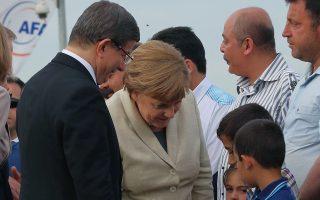 Η Αγκελα Μέρκελ μαζί με τον Αχμέτ Νταβούτογλου χαιρετούν προσφυγόπουλα από τη Συρία στο στρατόπεδο προσφύγων του Γκαζιαντέπ της Τουρκίας.