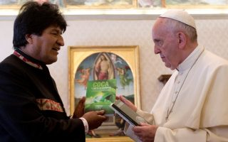 Pope Francis receives a gift from Bolivia's President Evo Morales during their meeting , on April 15, 2016, at the Vatican.  / AFP / POOL / ALESSANDRA TARANTINO