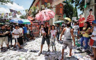 Πολίτες και παιδιά έξω από εκλογικό κέντρο στην πρωτεύουσα Μανίλα.