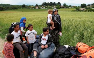 Πρόσφυγες από τον πρόχειρο καταυλισμό της Ειδομένης περιμένουν να επιβιβαστούν σε λεωφορείο, το οποίο θα τους μεταφέρει σε κάποιο χώρο φιλοξενίας.