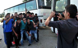 Λίγο πριν ξεκινήσει η προσπάθεια της αστυνομίας για την εκκένωση του καταυλισμού της Ειδομένης, πρόσφυγες και μετανάστες βγάζουν αναμνηστικές φωτογραφίες δίπλα στα λεωφορεία που θα τους μεταφέρουν σε οργανωμένα κέντρα φιλοξενίας. / AFP / SAKIS MITROLIDIS