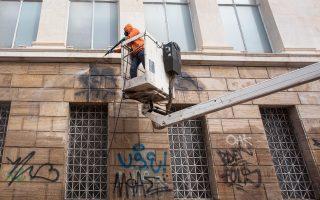 Εξειδικευμένα συνεργεία καθαρίζουν τους τοίχους της Εθνικής Βιβλιοθήκης από συνθήματα και μουντζούρες με σπρέι, χρησιμοποιώντας ειδικό αντιγκράφιτι υλικό, φιλικό προς το περιβάλλον, που προστατεύει τις επιφάνειες και μετά τον καθαρισμό τους.