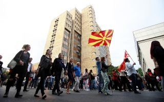 People wave national flags marching through a street in downtown Skopje, Macedonia, during an anti-government protest, Tuesday, May 10, 2016. Protests continue in the Balkan country almost every evening for nearly a month, after the country's president pardoned dozens of politicians who were facing criminal proceedings for alleged involvement in a wiretapping scandal. (AP Photo/Boris Grdanoski)