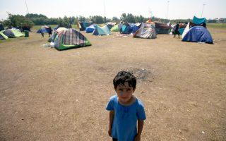 Προσφυγόπουλο ποζάρει στον φακό με φόντο τον πρόχειρο καταυλισμό του Χόργκος, στη βόρεια Σερβία, κοντά στα σύνορα με την Ουγγαρία. Περίπου 400.000 πρόσφυγες πέρασαν πέρυσι τα ουγγρικά σύνορα.