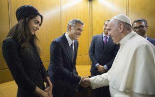Εντάξει, συγκεντρώνουν όπου και να πάνε τα βλέμματα και γι αυτόν το λόγο η σύζυγος του ηθοποιού George Clooney, αξιόλογη και διάσημη δικηγόρος η ίδια, Amal Alamuddin έχει έναν στυλίστα να την ντύνει. Τώρα γιατί στην διάρκεια επίσκεψης στο Βατικανό όπου θα συναντούσαν τον Πάπα Φραγκίσκο, θα έπρεπε να μοιάζει με κάθε ηλικιωμένη κυρία που πάει στηνκκλησία με τα καλά της (αγορασμένα πριν από 20 τουλάχιστον χρόνια) είναι άγνωστο.  EPA/L'OSSERVATORE ROMANO