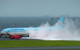 White smoke rises from an engine of a Korean Air jet as firefighters battle an apparent engine fire on the tarmac at Haneda Airport in Tokyo Friday, May 27, 2016 . All the passengers and crew were evacuated unharmed, Japanese media reported. (Hiroshi Miyamoto/Kyodo News via AP) JAPA OUT, CREDIT MANDATORY