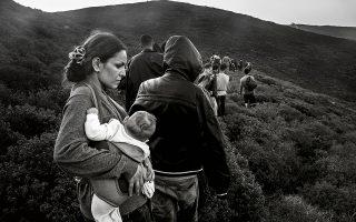 Φωτογραφία: Enri Canaj - Σύρια μητέρα κρατάει το 4 μηνών μωρό της καθώς φθάνει στις Οινούσσες αφού έχει διασχίσει με βάρκα τα θαλάσσια σύνορα Ελλάδας - Τουρκίας. Σεπτέμβριος 2015.