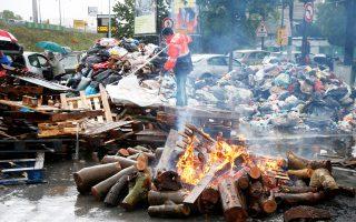 Απεργός των υπηρεσιών καθαριότητας της γαλλικής πρωτεύουσας, μέλος του CGT, μετά την κατασκευή οδοφράγματος έξω από τον χώρο υγειονομικής ταφής απορριμμάτων του Ιβρί-σουρ-Σεν.