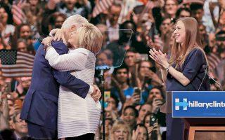Η Χίλαρι Κλίντον, στην αγκαλιά του συζύγου της Μπιλ, χειροκροτείται από την κόρη τoυς Τσέλσι, σε επινίκια συγκέντρωση στο Μπρούκλιν.