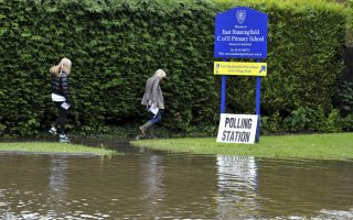People make their way along a flooded path as they arrive to vote at the polling station in East Hanningfield,  Essex, England, Thursday, June 23, 2016 as torrential downpours and flooding have swamped parts of London and the South East in the early hours of EU referendum day. Voters in Britain are deciding Thursday whether the country should remain in the European Union — a referendum that has exposed deep divisions over issues of sovereignty and national identity. (Nick Ansell/PA via AP)  UNITED KINGDOM OUT  NO SALES NO ARCHIVE