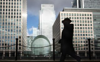 A businessman walks past offices in the financial district of Canary Wharf in London, U.K., on Monday, March 2, 2009. European stocks fell to the lowest level since 1996 on concern profits are deteriorating and banks will need more capital. Photographer: Jason Alden/Bloomberg News