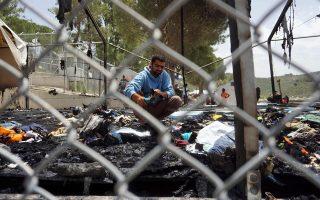 Πρόσφυγας ψάχνει στα αποκαΐδια μιας σκηνής σε hotspot στη Μόρια Λέσβου, έπειτα από περιστατικό που εγείρει ερωτήματα για τους όρους λειτουργίας των χώρων αυτών.