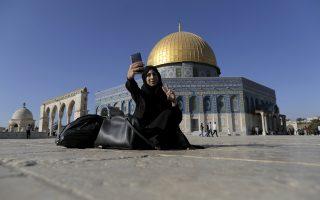 Νεαρή μουσουλμάνα τραβάει μια σέλφι μπροστά στον Ναό του Βράχου, στην Ιερουσαλήμ.