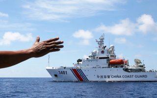 Ανησυχία για κλιμάκωση των εντάσεων στη Νότια Σινική Θάλασσα προκάλεσε η απόφαση του Διαιτητικού Δικαστηρίου της Χάγης –κατόπιν προσφυγής των Φιλιππίνων– ότι οι αξιώσεις της Κίνας στην περιοχή δεν νομιμοποιούνται από το Δίκαιο της Θάλασσας. Το Πεκίνο χαρακτήρισε «αστήρικτη και άκυρη» την απόφαση, ενώ ο Λευκός Οίκος την έκρινε «τελεσίδικη και δεσμευτική». Στη φωτογραφία, άνδρας (μη διακρινόμενος) του πολεμικού ναυτικού των Φιλιππίνων γνέφει σε σκάφος της κινεζικής ακτοφυλακής να μην πλησιάσει τα διαφιλονικούμενα ύδατα.