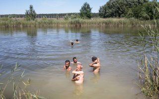 Μετανάστες και πρόσφυγες από το Αφγανιστάν κολυμπούν σε λίμνη  της Σερβίας, λίγα μέτρα από τα σύνορα με την Ουγγαρία.