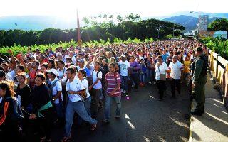 Κάτοικοι της Βενεζουέλας περνούν τα σύνορα από τη γέφυρα Μπολιβάρ, που συνδέει τη χώρα με την Κολομβία, προκειμένου να προμηθευτούν τρόφιμα και άλλα είδη πρώτης ανάγκης.
