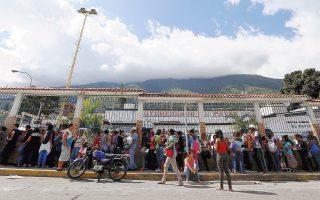 Πολίτες σε ουρά πολλών μέτρων έξω από σούπερ μάρκετ στο Καράκας της Βενεζουέλας, προκειμένου να αγοράσουν μαγειρικό λάδι και μαργαρίνη.