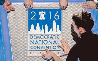 Αφίσα για το συνέδριο του Δημοκρατικού Κόμματος, που ξεκίνησε χθες στη Φιλαδέλφεια, τοποθετείται πάνω στο βήμα. Παρά τα ηχηρά ονόματα που θα ανεβούν στη σκηνή, η ηχηρότερη «παρουσία» είναι αυτή του Ρεπουμπλικανού Ντόναλντ Τραμπ, που εμφανίζεται να προηγείται της Χίλαρι Κλίντον σε δύο δημοσκοπήσεις.