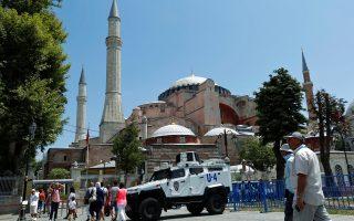 Τουρίστες περνούν δίπλα από τεθωρακισμένο της τουρκικής αστυνομίας έξω από την Αγία Σοφία.