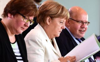 German Chancellor Angela Merkel (C) leafs through documents next to German Chief of Staff Peter Altmaier (R) during a weekly meeting of the German cabinet at the Chancellery in Berlin on July 13, 2016.  / AFP / JOHN MACDOUGALL