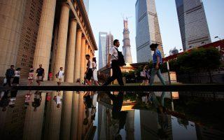 Πολίτες βηματίζουν προς τον σταθμό του μετρό στη χρηματοοικονομική περιοχή Πουντόνγκ της Σαγκάης.