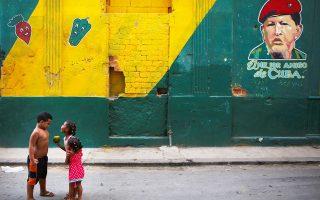 Παιχνίδια στο δρόμο με φόντο τον «καλύτερο φίλο της Κούβας», όπως λέει το γκράφιτι με τον Ούγκο Τσάβες σε τοίχο της Αβάνας. (Reuters/ Alexandre Meneghini))