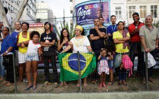 Πολίτες του Ρίο περιμένουν να δουν από κοντά τη διέλευση της Ολυμπιακής Φλόγας στον δρόμο προς το στάδιο Μαρακανά της πόλης, όπου θα πραγματοποιηθεί αύριο η τελετή έναρξης των Αγώνων.