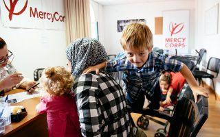 Ο μικρός Σάμι παίζει, ενώ η μητέρα του συζητά με υπαλλήλους της Mercy Corps, στη Μυτιλήνη. Η οργάνωση δραστηριοποιείται σε περισσότερες από 40 χώρες- Credit: Corinna Robbins / Mercy Corps