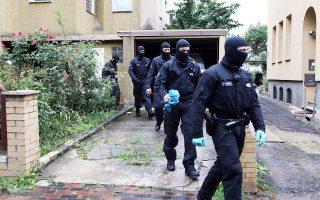 Μασκοφόροι αστυνομικοί ερευνούν σπίτι στο Χίλντεσχαϊμ της Γερμανίας.