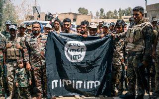 Μέλη σουνιτικής πολιτοφυλακής επιδεικνύουν λάφυρο, μια σημαία του Ισλαμικού Κράτους.
